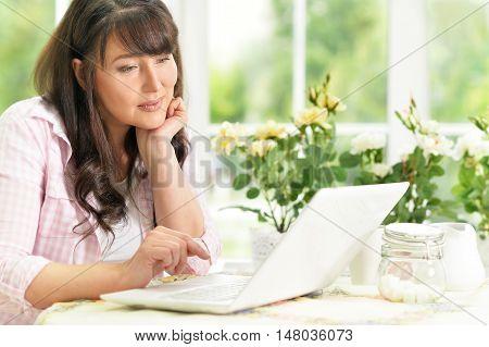 Senior woman portrait with laptop at home