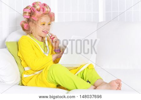 Happy cute little girl in hair curlers and laptop