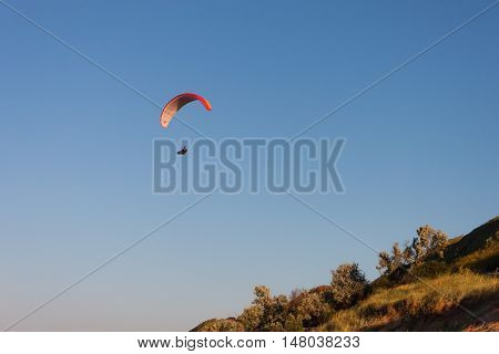 Paragliders flying across the sky above the hills