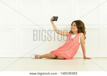 portrait of cute little girl  in beautiful dress with mobile phone taking selfie photo