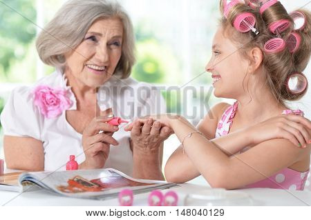 Cute little girl in  hair curlers  with granny  with magazine and nail polish