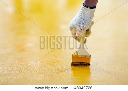 Hand with brush and yellow paint in construction site