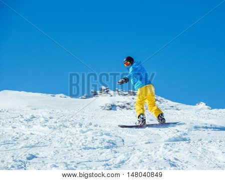 Snowboarder at the winter ski resort moving down the hill