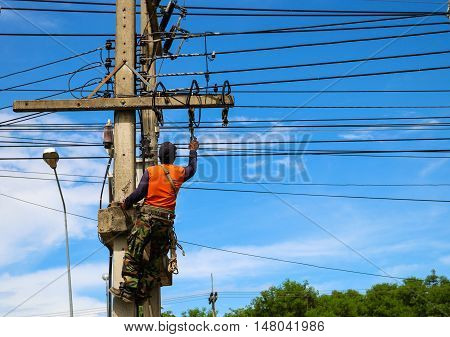 Electrician repair electric transformers with blue sky.