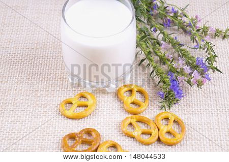 Glass of milk and crackers. Transparent glass of milk with cookies and wildflowers. Milk with blue flowers.
