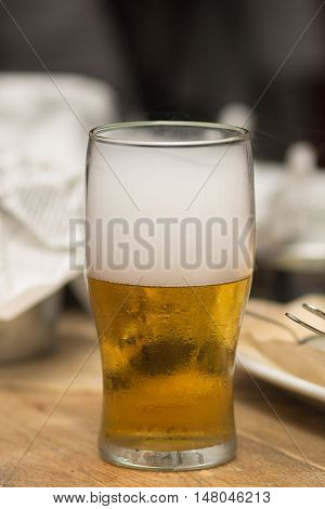 Misted glass of beer on top filled with white smoke