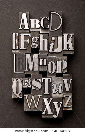 Alphabet photographed using a mix of vintage letterpress characters on a black textured background.