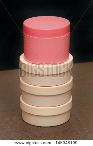 Stack of closed beige and pink plastic toiletries containers