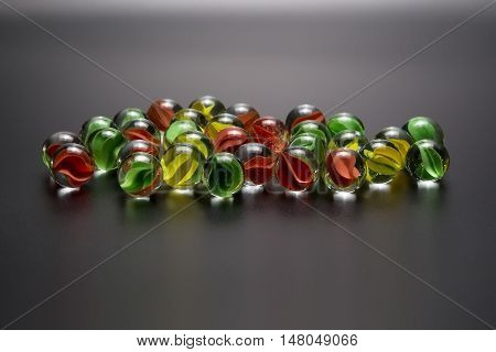 Group of colored glass balls on a dark gray background closeup