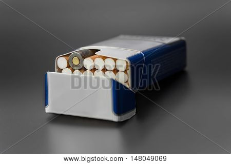 a pack of cigarettes with one live ammunition in a pack on a white background isolated