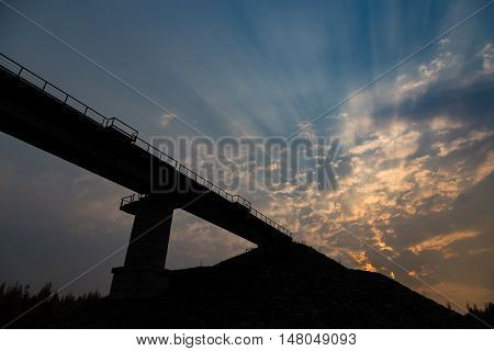rays of sunset on a cloudy sky with the silhouette of a railway bridge