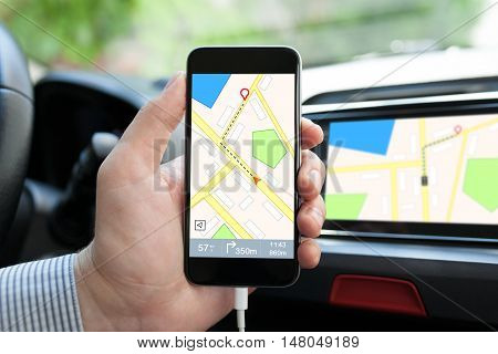 man hand in the car holding phone with navigation map and on the screen multimedia system