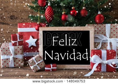 Colorful Card For Seasons Greetings. Christmas Tree With Balls And Snowflakes. Gifts Or Presents In The Front Of Wooden Background. Chalkboard With Spanish Text Feliz Navidad Means Merry Christmas