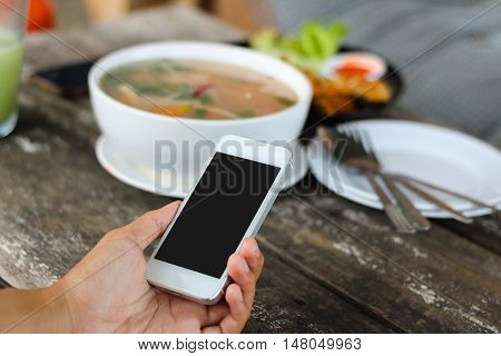 Woman use mobile phone in coffee shop view from backside and meal background.
