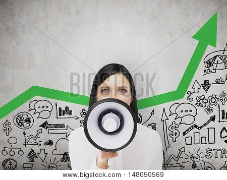 Portrait of business coach shouting with megaphone and standing near concrete wall with green arrow and startup sketch. Toned image
