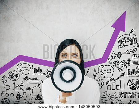 Portrait of business lady talking with a megaphone near her face. Concept of business coaching. Toned image
