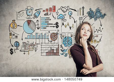 Portrait of businesswoman in red dress standing near concrete wall with startup sketch and working out her business plan. Concept of strategy. Toned image