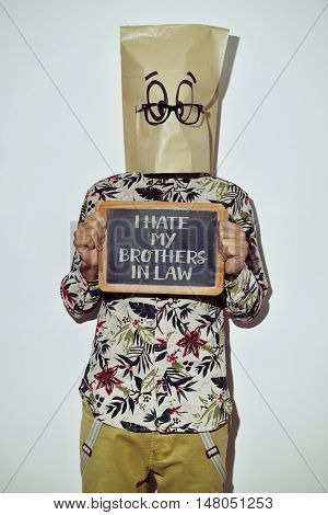 a young man dressing casual wear with a paper bag in his head shows a chalkboard with the text I hate my brothers in law written in it