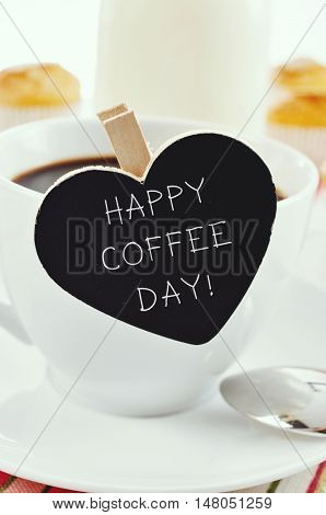 the sentence happy coffee day written in a heart-shaped blackboard placed in a cup of coffee