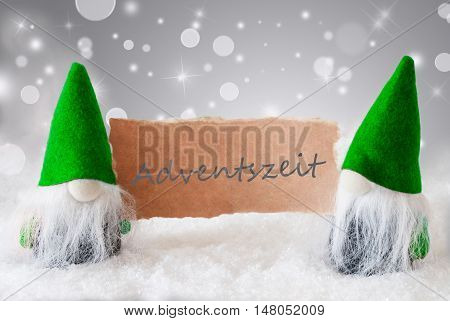 Christmas Greeting Card With Two Green Gnomes. Sparkling Bokeh And Noble Silver Background With Snow. German Text Adventszeit Means Advent Season
