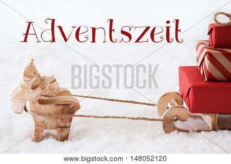 Moose Is Drawing A Sled With Red Gifts Or Presents In Snow. Christmas Card For Seasons Greetings. German Text Adventszeit Means Advent Season