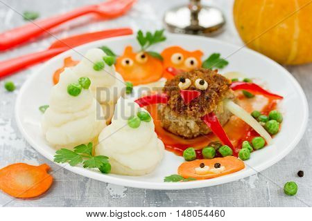 Fun and healthy idea for kids lunch or dinner on Halloween meal - meat cutlet in the form of a spider mashed potatoes ghosts and colorful vegetable garnish on plate