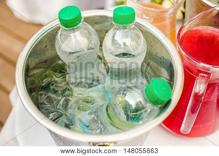 Bottled water in an ice bucket and a jug with juice