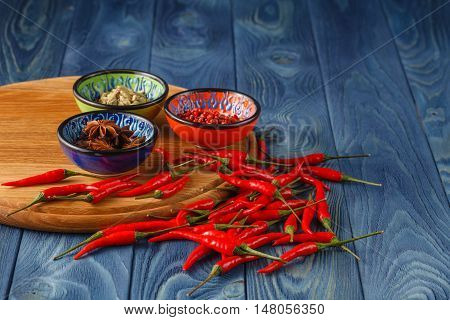 Cayenne Pepper And Red Peppers On Old Wooden Table