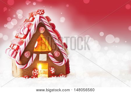 Gingerbread House In Snowy Scenery As Christmas Decoration. Candlelight For Romantic Atmosphere. Red Background With Snowflakes. Copy Space For Advertisement