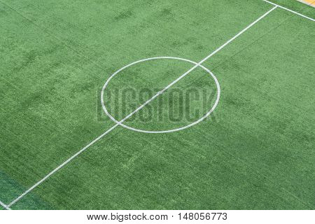 Green artificial grass soccer field with white line and center circle.