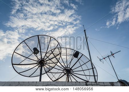 Two black satellite dishes on the rooftop with beautiful blue sky and white clouds in sunny day.