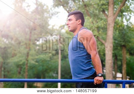 fitness sport exercising training and lifestyle concept - young man doing triceps dip on parallel bars outdoors