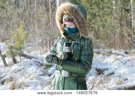 Concentrated girl is wearing green shiny down coat opening stainless steel thermos flask in winter frosty wood outdoors