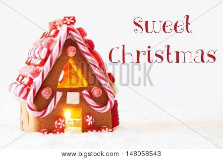 Gingerbread House In Snowy Scenery As Christmas Decoration With White Background. Candlelight For Romantic Atmosphere. English Text Sweet Christmas