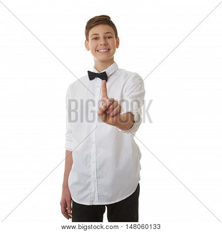 Cute teenager boy in white shirt and black bow tie pushing something in front himself over white isolated background, half body