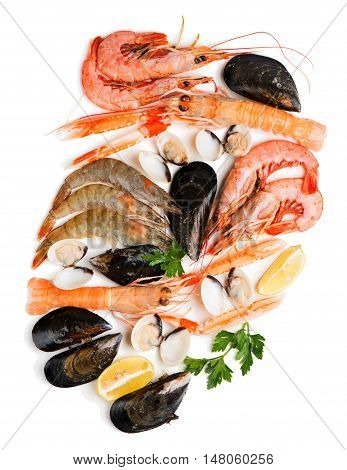 Top view of uncooked seafood (langoustine shrimp shellfish mussel clam) decorated with lemon and parsley isolated on white background.