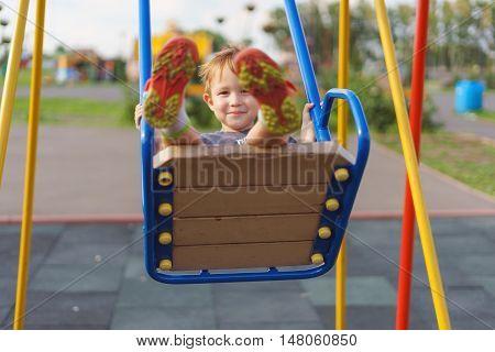 Boy swinging on a swing in the playground. Warm summer evening children activities.