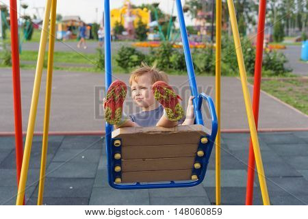 Boy swinging on a swing in the playground. A warm summer evening children activities.
