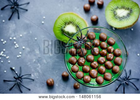 Green kiwi jelly with chocolate candy balls on Halloween