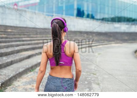 Rear view of a sporty woman listening to the music.