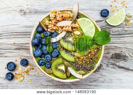 Matcha green tea breakfast superfoods smoothies bowl topped with chia flax and pumpkin seeds bee pollen granola coconut flakes kiwi and blueberries. Overhead top view flat lay