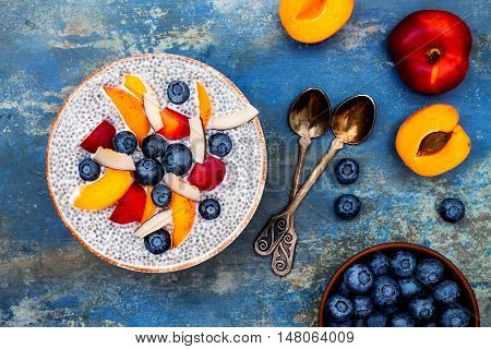Detox and healthy superfoods breakfast bowl concept. Vegan coconut milk chia seeds pudding over blue stone table with various fruits and blueberries. Overhead top view flat lay.