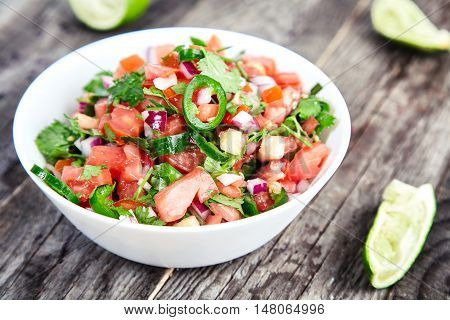 Delicious, spicy sauce Pico de Gallo also called salsa Fresca. Traditional recipe, fresh tomatoes, red onion, cilantro, lime juice and spicy jalapenos. National Mexican cuisine. Wood rustic background
