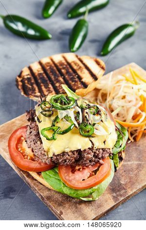 Gourmet homemade burger with juicy beef, fried spicy jalapenos, fresh spinach, sliced tomatoes, melted cheese and grilled bun. With fresh, crunchy coleslaw on wooden board. Blurred jalapenos behind