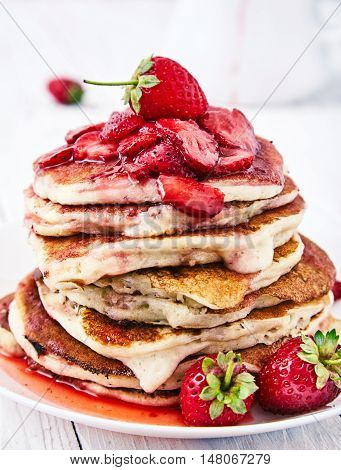 Stack of american pancakes with sliced strawberries and strawberry jam on a white plate. Delicious breakfast for whole family on white wood background, a white pitcher and fresh strawberries near it