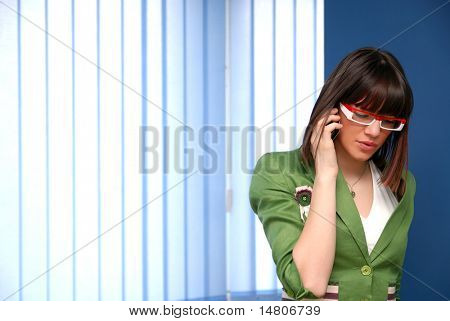 .youn businesswoman in green suit talking by telephone