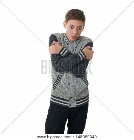 Cute teenager boy in gray sweater trying get warmer over white isolated background, half body