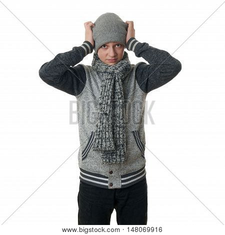 Cute teenager boy in gray sweater, hat and scarf with hands on head over white isolated background, half body