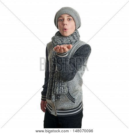Cute teenager boy in gray sweater, hat and scarf blowing on hands over white isolated background, half body