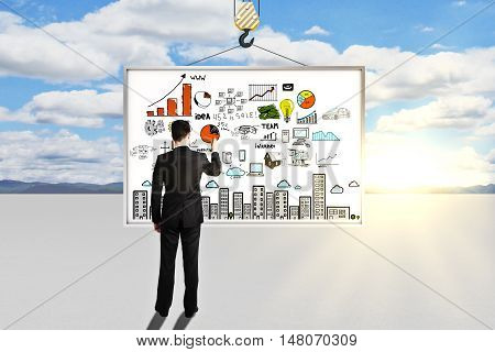 Back view of young businessman in suit drawing colorful business sketch on abstract whiteboard suspended on crane hook. Bright sky with sunshine in the background. Success concept